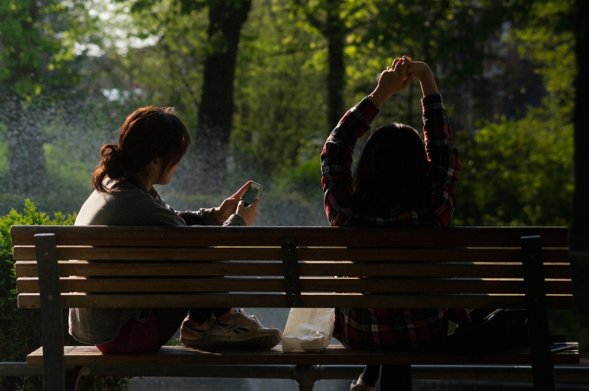 friends on bench with phones