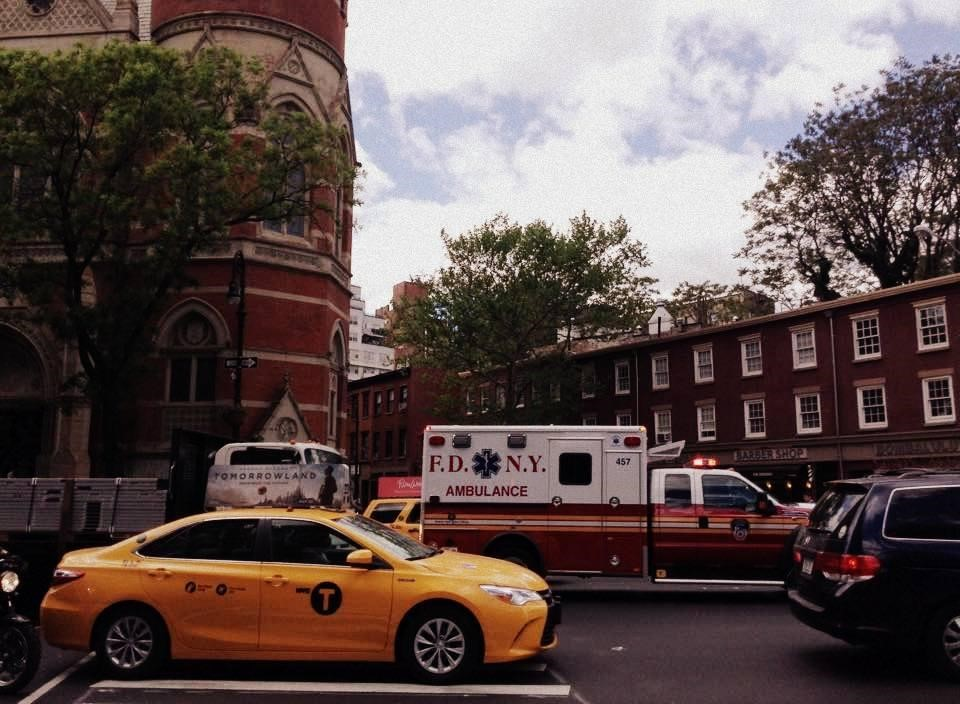 An ambulance attempts to get through heavy traffic on Sixth Avenue